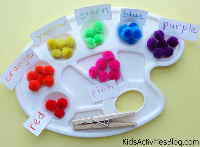 Color sorting game for preschoolers using red, orange, yellow, green, blue, and purple pom poms with clothes pins and paint palettes.
