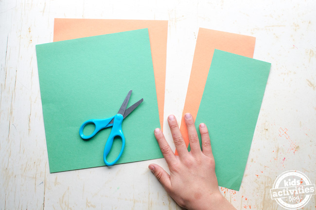make an Irish flag craft step one - cut off 1/3rd of each of the green and orange paper