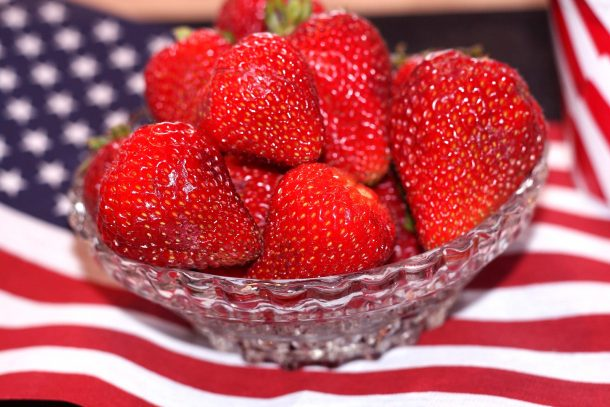 fresh strawberries in a bowl on an American flag for the 4th of July