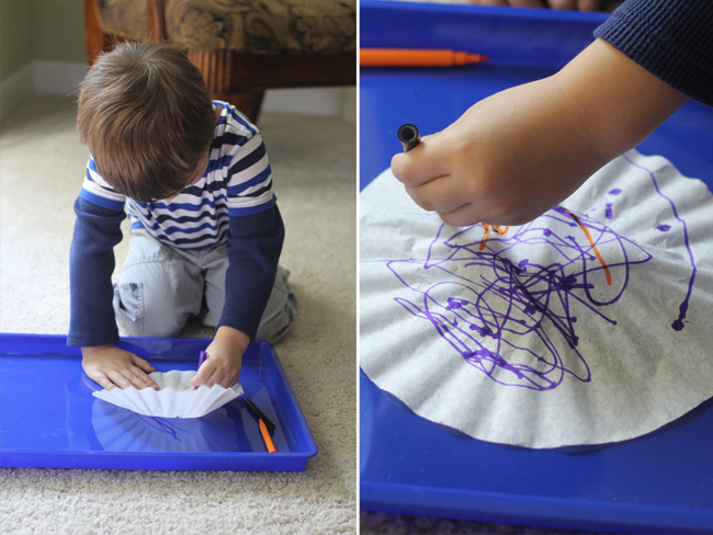 Halloween Jack-O-Lantern Art Project for Kids- a little boy coloring a coffee filter with purple and orange markers.