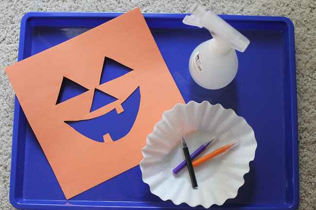 Halloween Jack-O-Lantern Art Project for Kids with orange construction paper with a jack o lantern face cut out, coffee filter, markers, and a spray bottle.