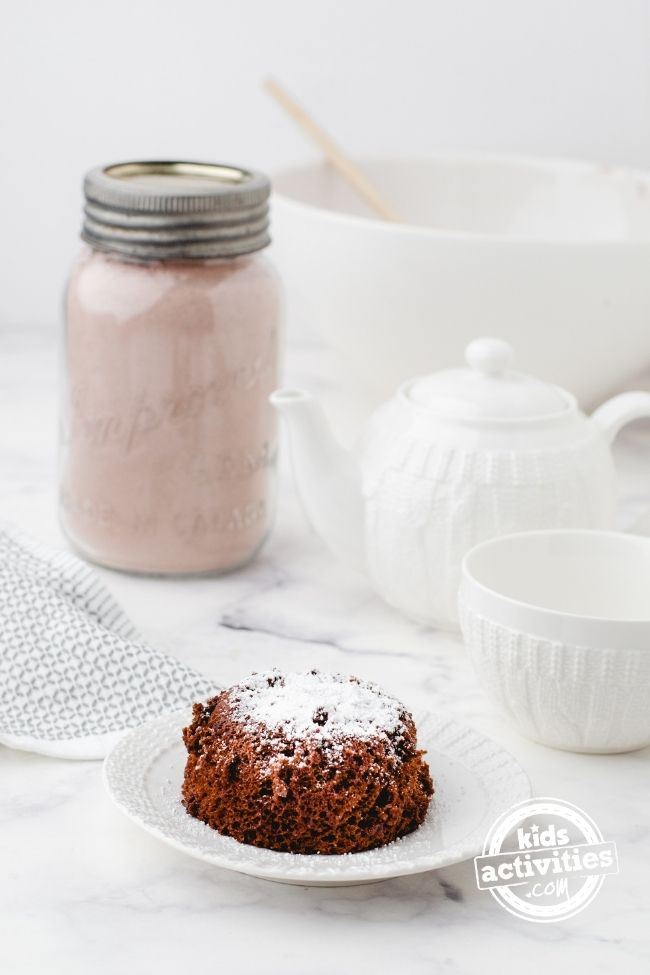 Hot chocolate mug cake mix and cake - kids activities blog - finished mug cake shown turned up side down on a plate sprinkled with powdered sugar and canning jar of cake mix in the background