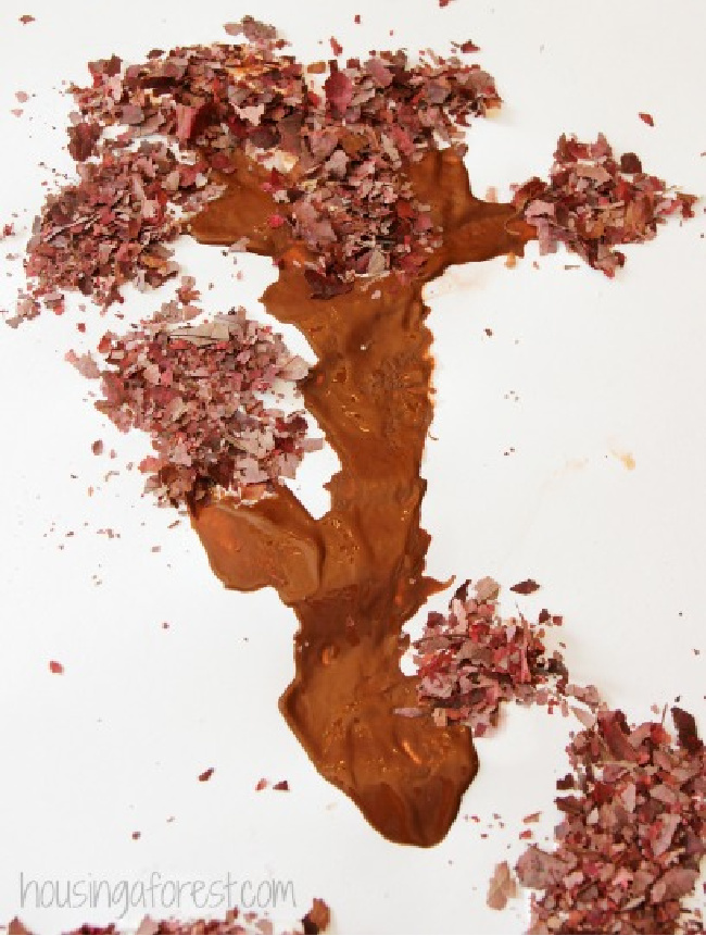 Autumn tree craft with brown paint and tree trunk shavings on a white paper.