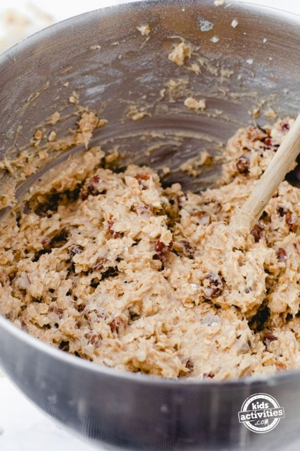 The sticky, yummy oatmeal raisin breakfast cookie dough in a stainless mixing bowl.
