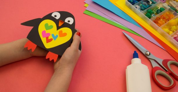 Penguin craft to make a little black penguin with a yellow tummy with green, orange, red, pink, and blue hearts in the middle.