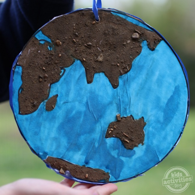 Earth day art that looks like the world, the ocean is blue, and land masses are covered with dirt.
