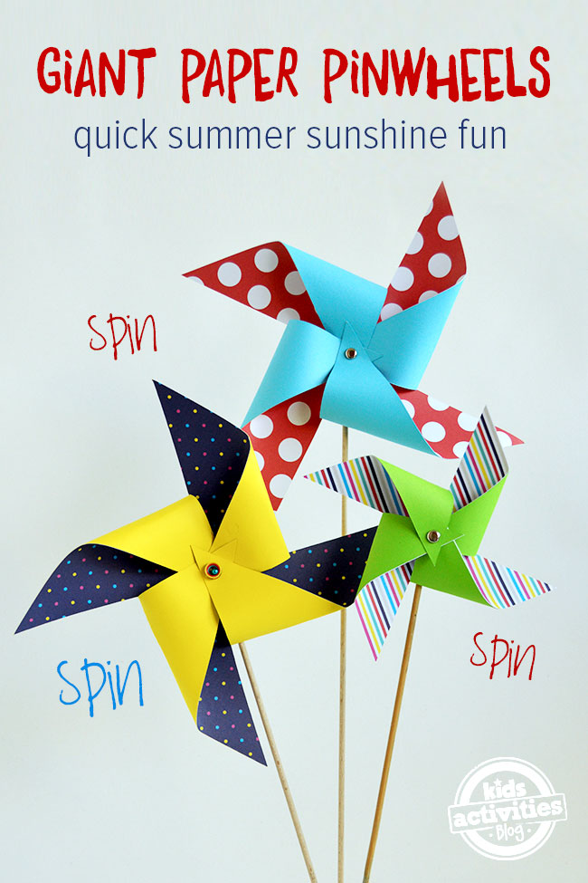giant diy paper pinwheels - three spinning paper pinwheels on wooden dowels shown