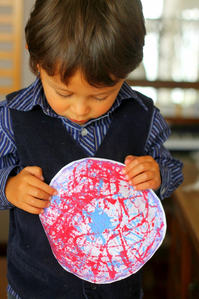 Memorial Day craft for kids - fireworks marble painting shown with preschool age boy on paper plate