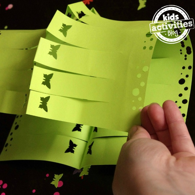 How to use a paper punch to create butterflies and large and small dots on a green paper lantern that is being folded by a small hand.