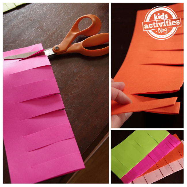 Craft paper punches make mini paper lanterns that are being cut by orange scissors. There are 4 flameless paper lanterns with the colors: pink, orange, white, and green.