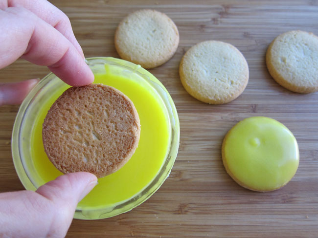 Dip Cookies In Lemon Frosting that is warmed up in a frosting tub.