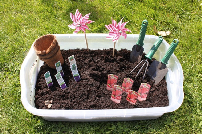 Plastic sensory bin full of dirt, seeds, and gardening tools on a patch of grass.
