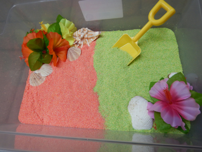 Plastic bin full of edible green and pink sand with shells and tropical flowers and a yellow plastic shovel.