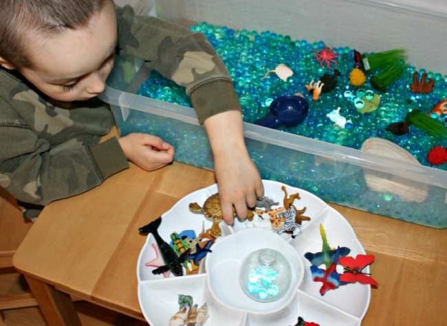 Little boy playing with various plastic toys in a plastic bin full of blue water beads on a wooden table.