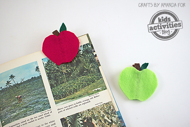 Apple Bookmark Craft that is read and green and clipped on a book.
