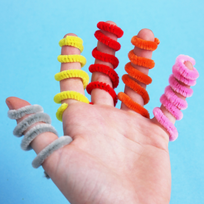 An assortment of pipe cleaners shown on the fingers of a child - Kids Activities Blog