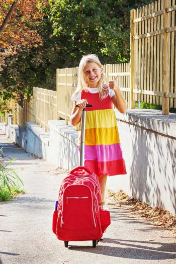 A girl in a colorful dress standing on the sidewalk next to her red rolling backpack.