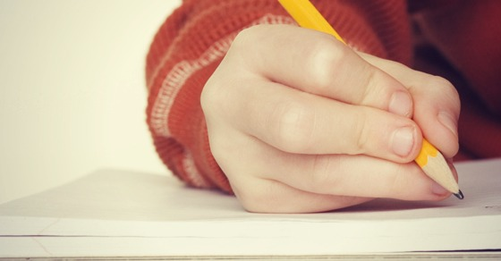 Wrong way to hold a pencil - common incorrect position kids often use - four fingers clench the pencil instead of three - shown writing improperly on notebook paper