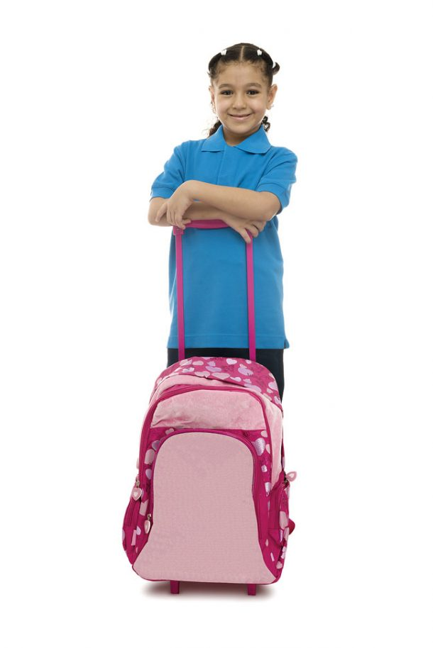 A young girl wearing a blue uniform and placing her arms and hands on the handle of a pink rolling bacpack.