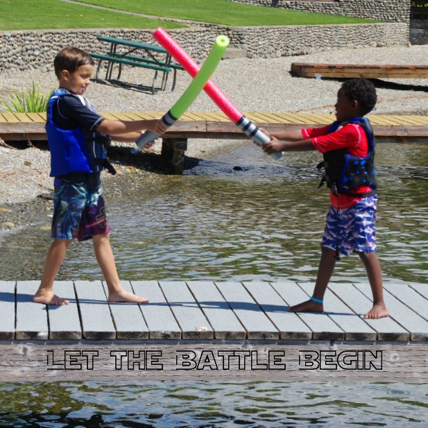 Become a Jedi or Sith with these pool noodle lightsabers that are red and green being battled by two boys on a dock.