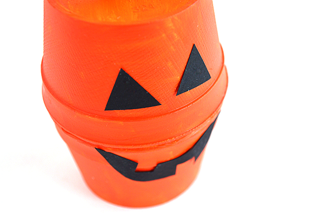 halloween treat boxes made of orange painted foam cups with a black mouth and eyes glued on