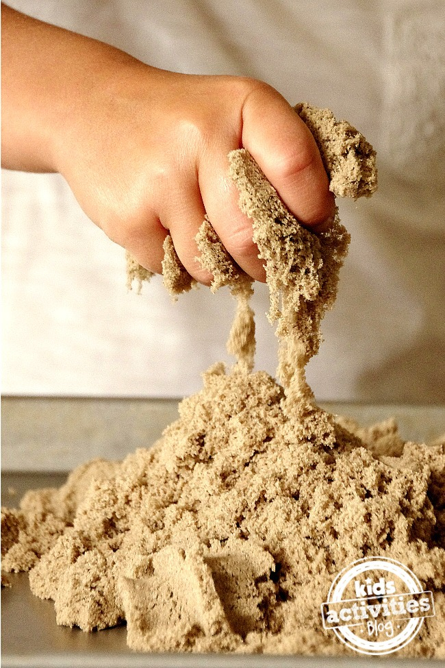 How does kinetic sand work? A child squishes the kinetic sand with his hand.