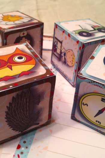 Story Adventure dice that have owls, clocks, fire, a jeep, and a hot air balloon.