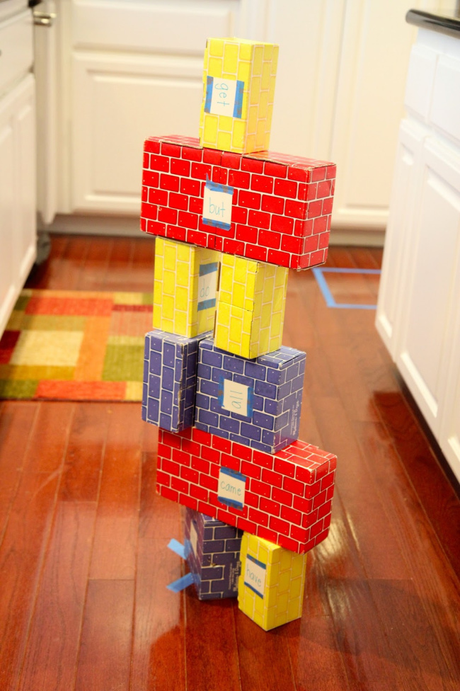 Knock down blocks sight word game with sight words written on colorful stacked blocks on a wooden floor.