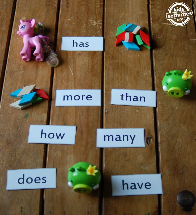 Math sight word game with sight word cards and toys forming sentences on a wooden background.