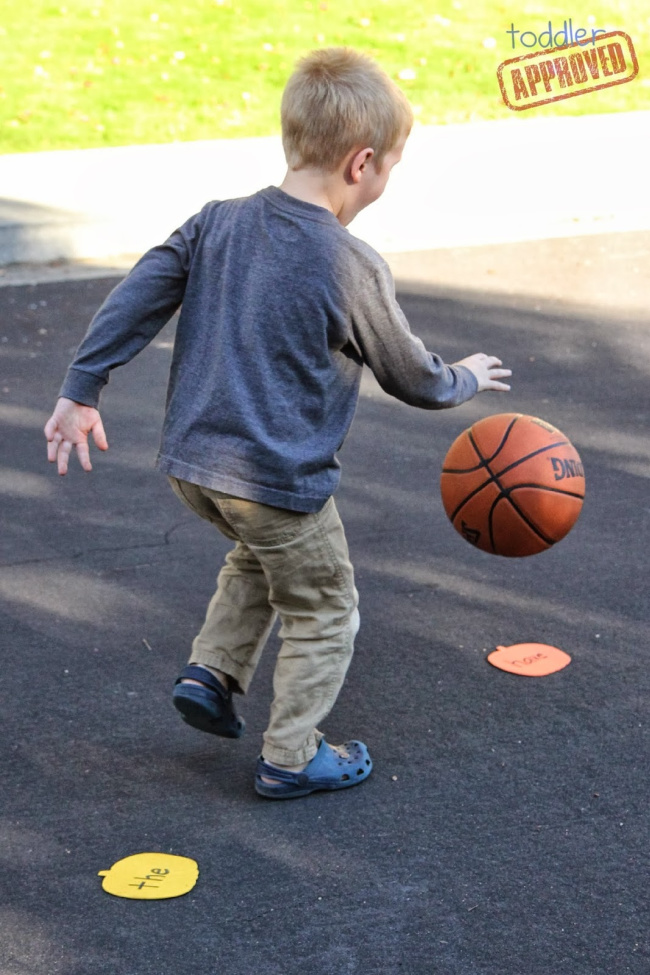 Sight word basketball game with a little boy dribbling a basketball on sight word cards placed on a driveway.