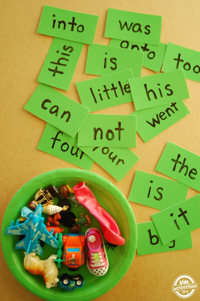 Sight words written on green cards on and spread out on a yellow table next to a green bowl of various toys.