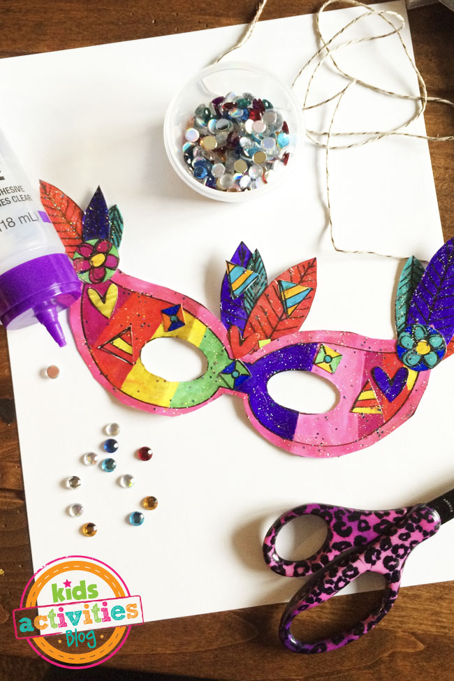 Mardi Gras mask craft from Kids Activities Blog - finished mask with colorful flowers and feathers with beads and craft supplies