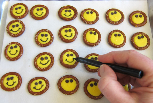 Add smiles using black food gel pen to the smiley pretzel treats that are yellow faced with black eyes.