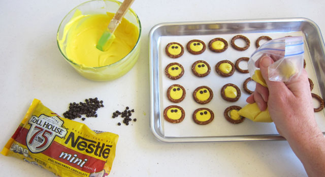 How to make smiley pretzel treats by using yellow melted white candy melts with yellow candy coloring and squeezing it into pretzel rounds and adding 2 mini chips for eyes.