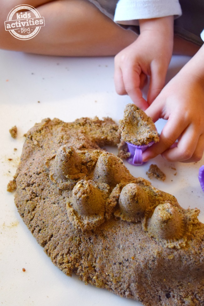 DIY kinetic sand made with slime and paly sand. It is being played with using purple plastic toys by little hands.