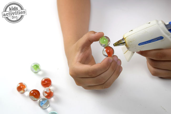 A child holding a red and green marble as they begin hot gluing them together.