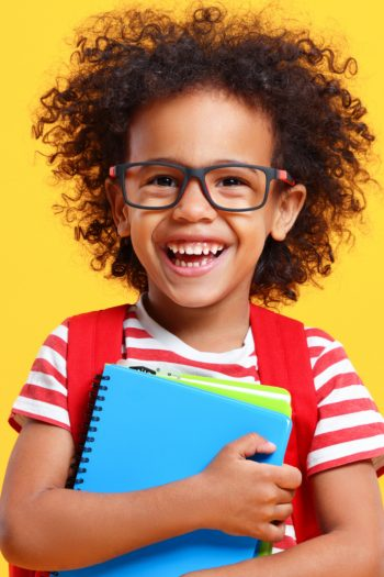 child laughing holding a notebook - back to school jokes for kids