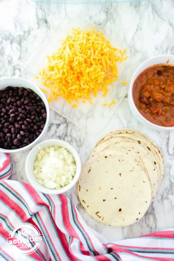 Shredded cheese, bowl of black beans, bowl of chopped onions, bowl of chili, and a pile of corn tortillas sitting on a marble countertop.