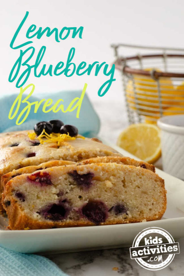 Lemon Blueberry Bread sliced and sitting on a white platter with a basket of lemons behind.