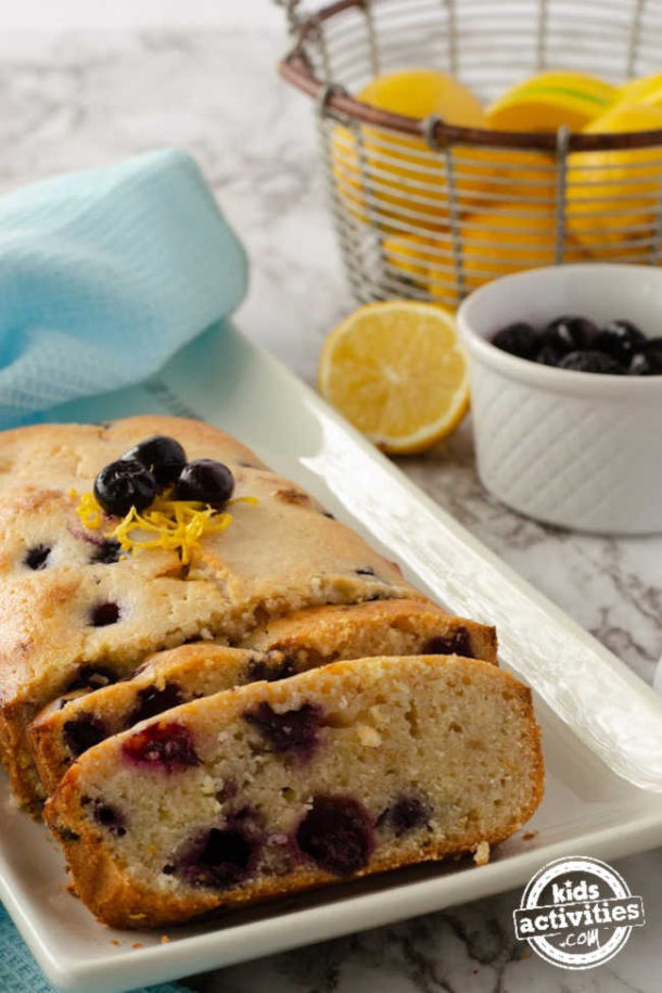 blueberry bread with frozen berries on a plate with fresh blueberries on top, lemon zest, next to a bowl of blueberries and a basket of lemons.