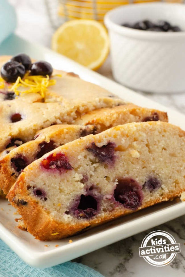 best lemon blueberry bread on a white glass plate topped with lemon zest and fresh blueberries.