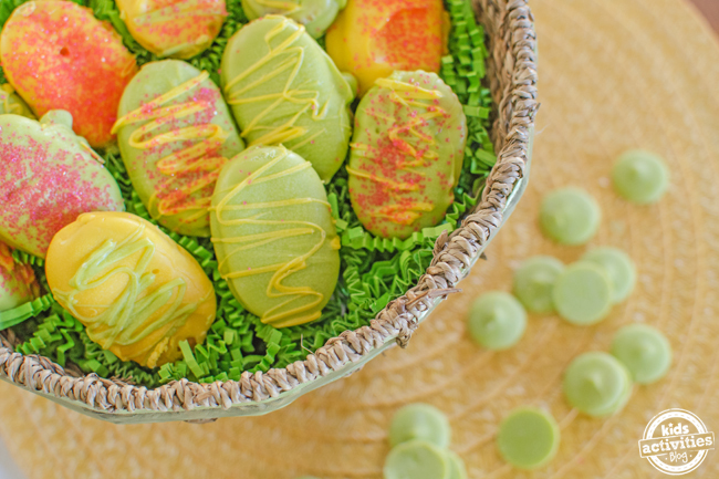 Easter cookies made with crackers with nutella in between them dipped in green and yellow white chocolate drizzled with yellow and green white chocolate with pink sprinkles.
