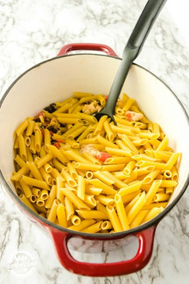 Adding dry pasta to the one pot pasta recipe.