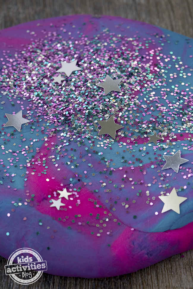 Adding glitter to playdough can make a beautiful galaxy effect like with these small pieces of glitter and start glitter on the pink, purple, and blue playdough.