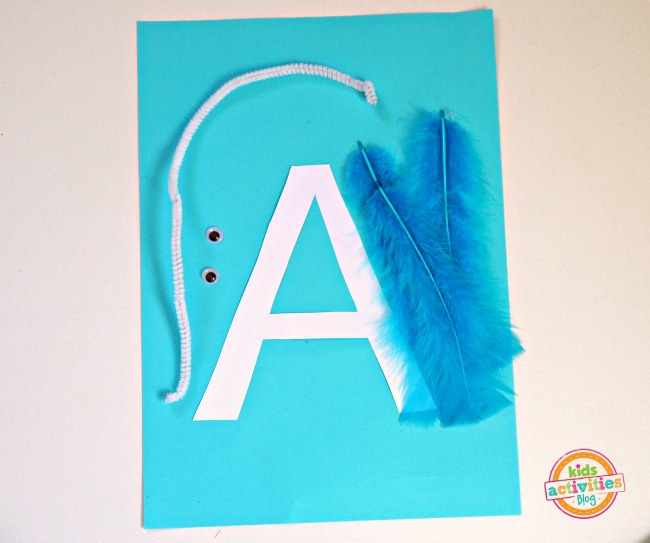 letter a craft out of craft paper with feather and googly eyes