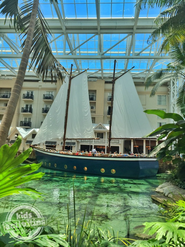 Gaylord Palms Pirate Ship full of people with fauna all around in shallow water.