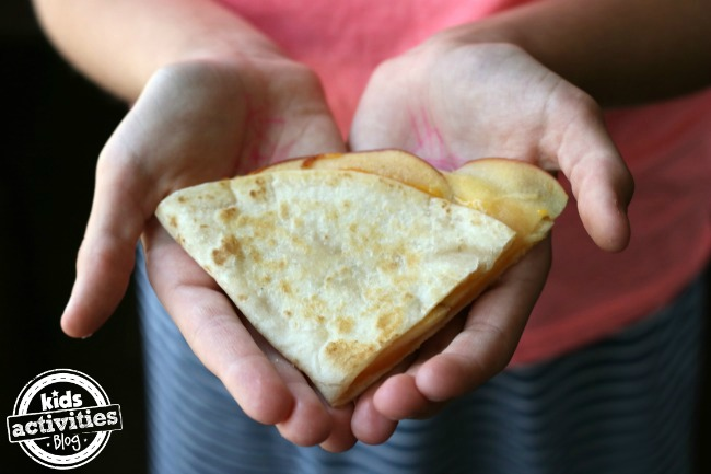 5 Back to School Afternoon Snack Ideas - apple quesadilla being held in hand by child