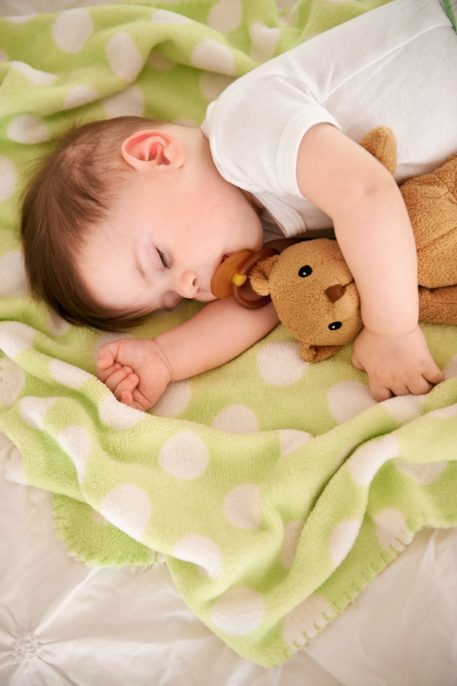 Cropped shot of an adorable baby boy holding his teddy while sleeping