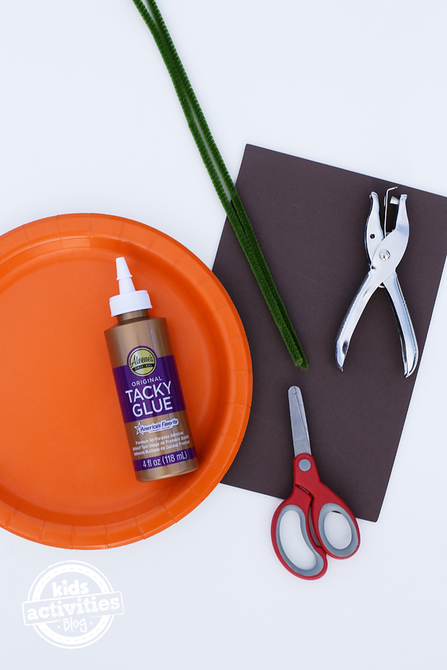 Tacky glue bottle sits on top of an orange paper plate. To the side are scissors, green pipe cleaners, a hole punch, and brown craft foam.