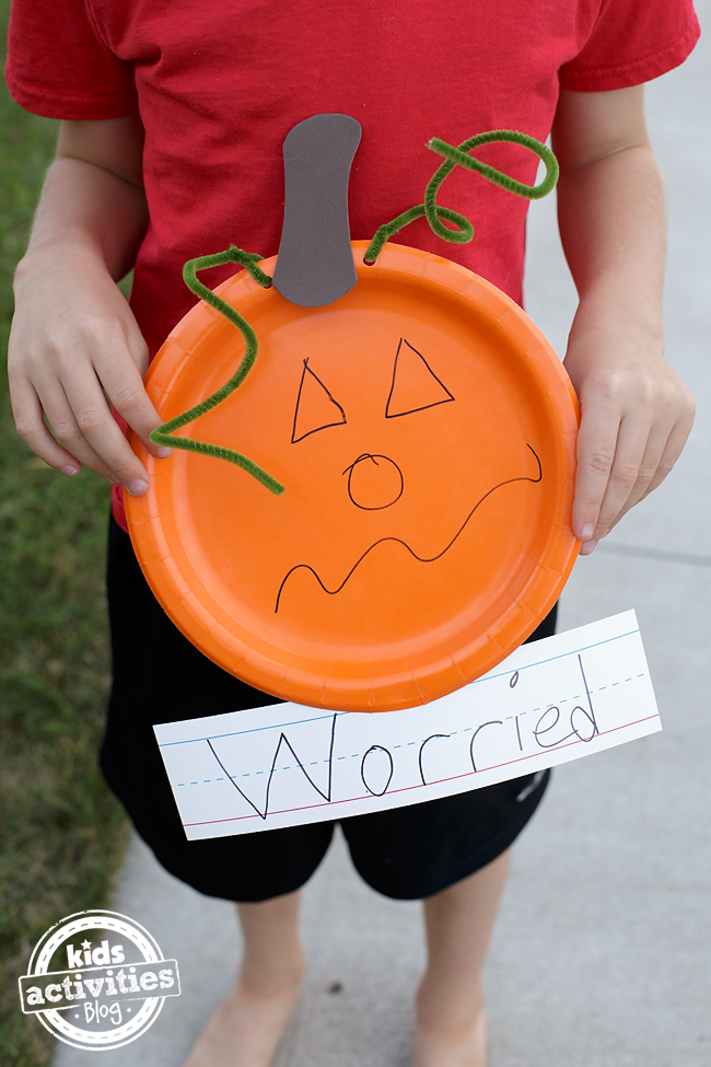 Young boy holds up his homemade paper plate pumpkin with the word worried underneath it.